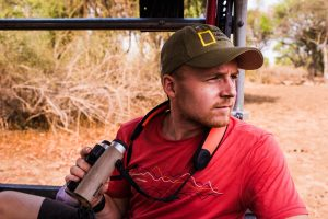 Martin Edström, photographer, journalist and National Geographic Explorer, sitting in the back of a landrover looking for lions in a remote part of South Luangwa National Park, Zambia.