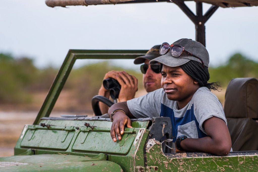 National Geographic Explorer Thandiwe Mweetwa (front) and Zambia Carnivore Programme director Matt Becker (back) looking at a pride of lions. Spending most of their time in the field, they track the movement and dynamics of lions and other carnivores - like wild dogs and hyenas - throughout South Luangwa National Park and other sites in Zambia.